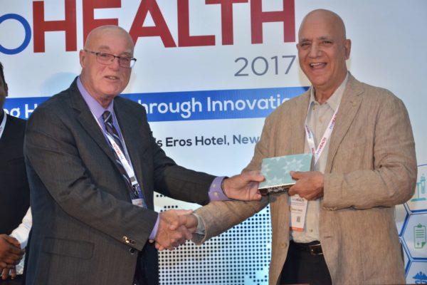 Dr Ronald Heslegrave presenting a memento to Dr Shiban Ganju at InnoHEALTH 2017