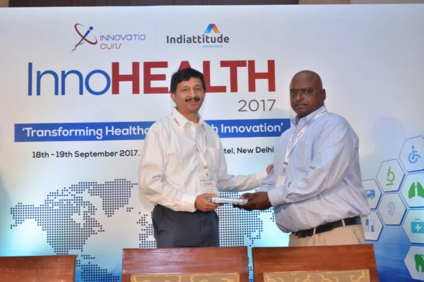 Sandipan Gangopadhyay presenting a memento to Reggie George at InnoHEALTH 2017