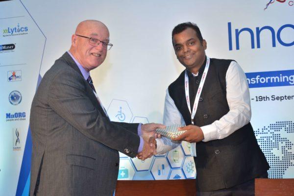 Dr Ronald Heslegrave presenting a memento to Ashish Gupta at InnoHEALTH 2017